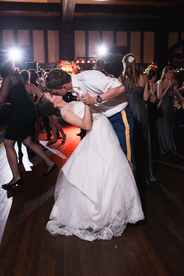 groom dips and kisses bride while dancing at reception