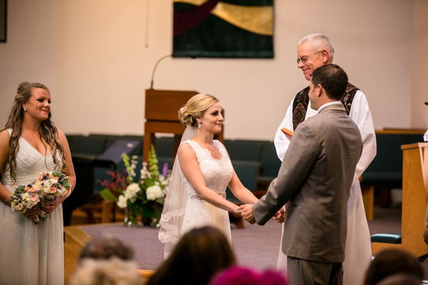 bride and groom hold hands during Catholic wedding ceremony