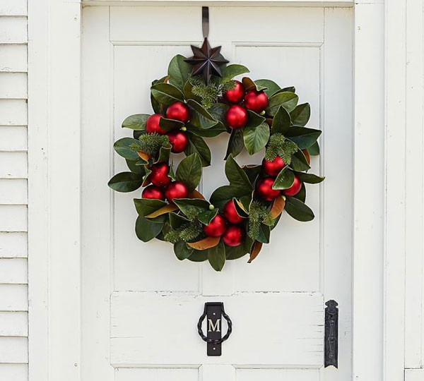 Christmas wreath with magnolia leaves and bright red ornaments