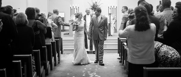 bride and groom smile and walk back down aisle after ceremony concludes