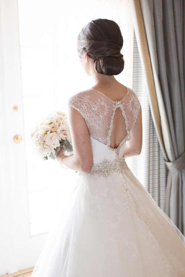 back of wedding dress featuring lace cap sleeves and beaded sash