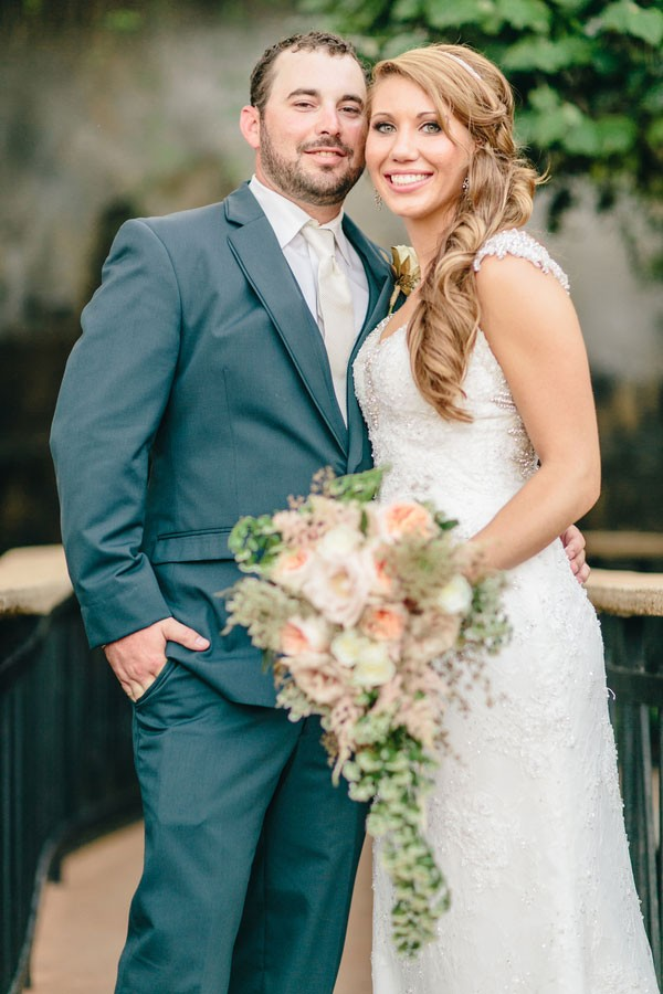 bride wearing wedding dress with cap sleeves and groom in charcoal gray suit with white tie