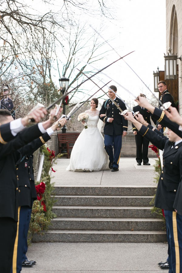bride and groom walk under swords held by uniformed men