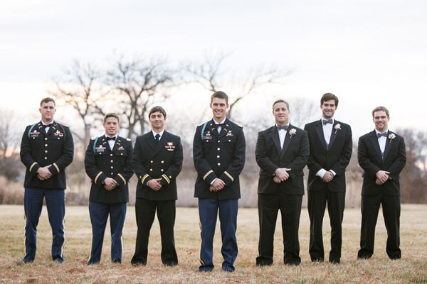 groom and groomsmen in military uniform and dark tuxedo suits