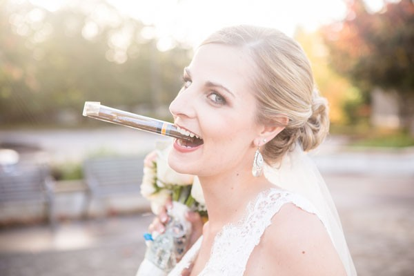 bride jokingly pretends to smoke a wrapped cigar