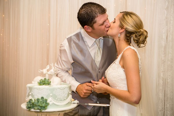bride and groom kiss after feeding each other wedding cake