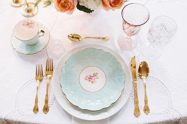 vintage place setting with pale blue plate and gold flatware