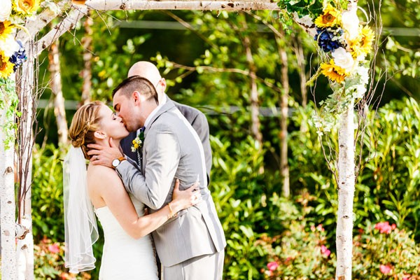 groom in pale gray suit kisses bride with veil