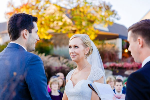 bride smiles at groom during outdoor ceremony in fall