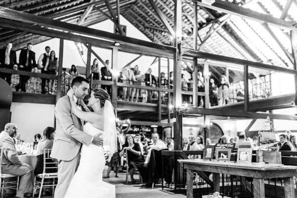 bride and groom dance in rustic wedding venue