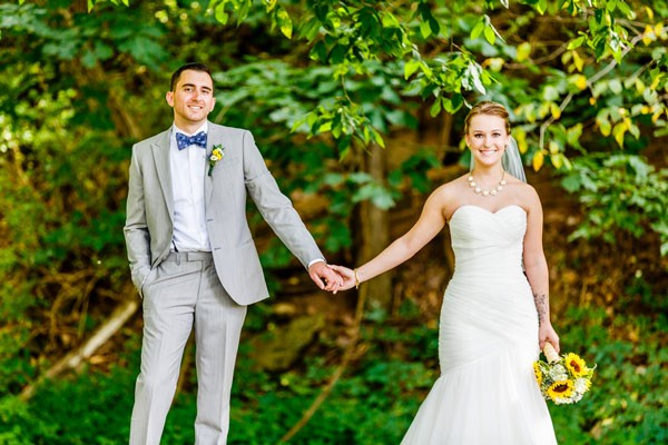 bride in strapless wedding dress holding hands with groom in a blue bow tie