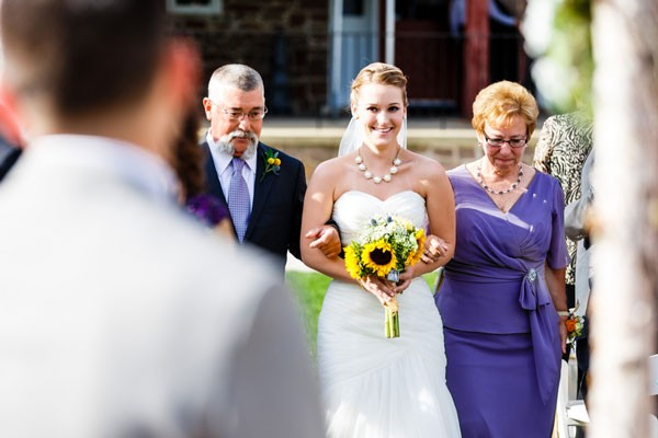 bride with bib necklace and strapless gown walks down aisle with parents