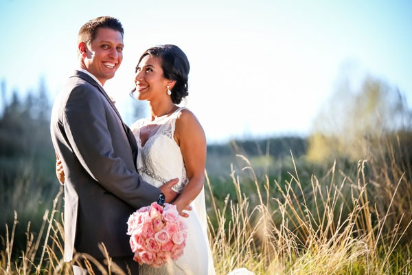 bride and smiling groom in field of tall grass