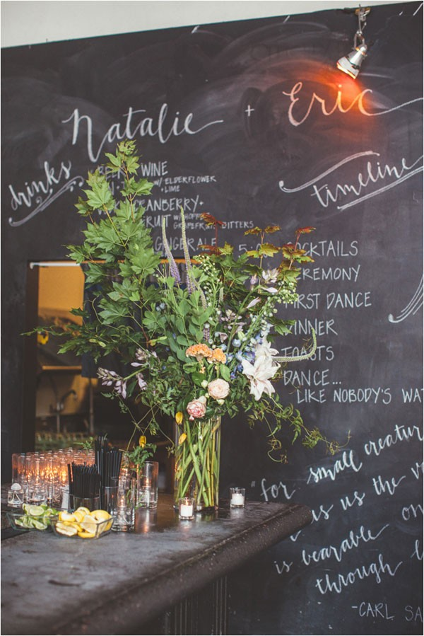large floral arrangement in front of chalkboard wall at wedding venue