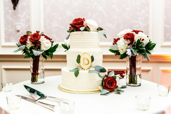 traditional wedding cake with red and white bridesmaid bouquets and floral decor