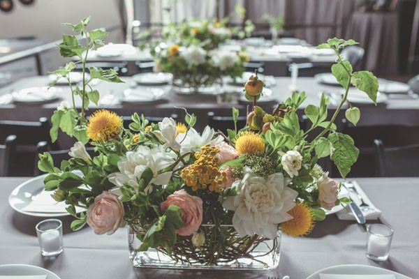 long wedding centerpiece with roses on gray linens