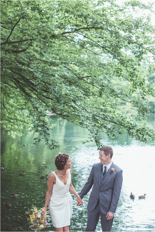bride in short white dress and groom standing by Willamette River
