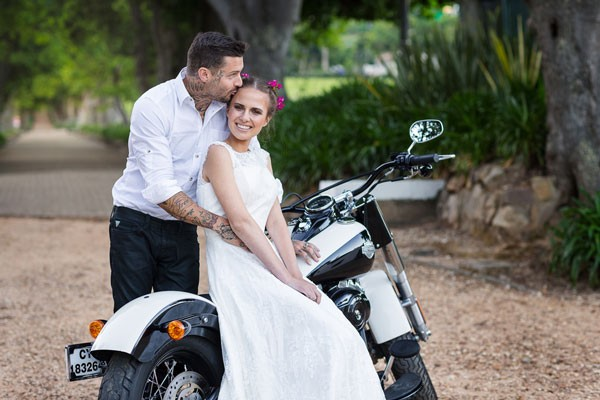 groom kisses bride while she is sitting on white motorcycle