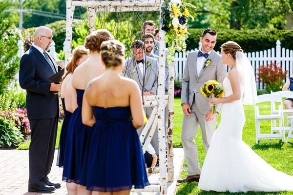 bridesmaids in navy dresses and groomsmen in gray suits at altar with couple in outdoor wedding ceremony