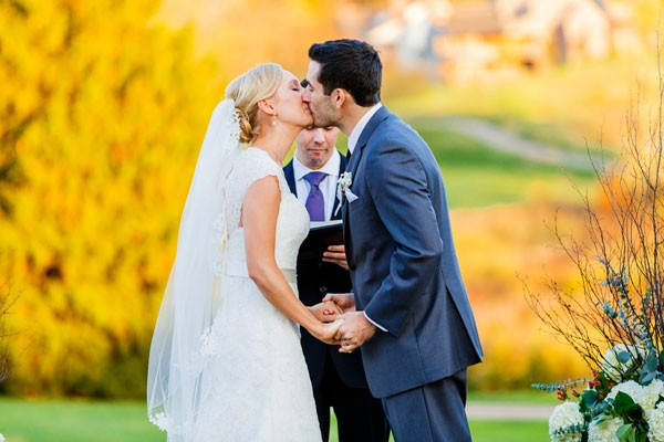 groom kisses bride at outdoor fall wedding ceremony