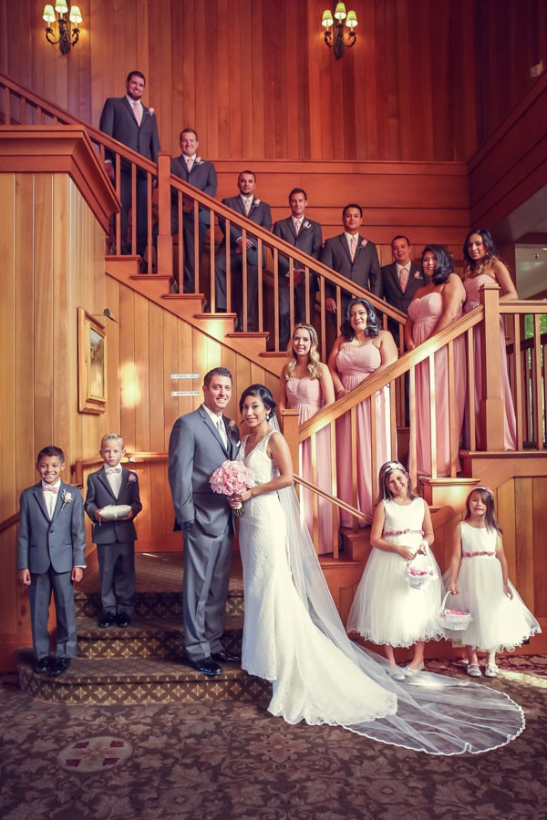 portrait of wedding party lining large staircase at venue