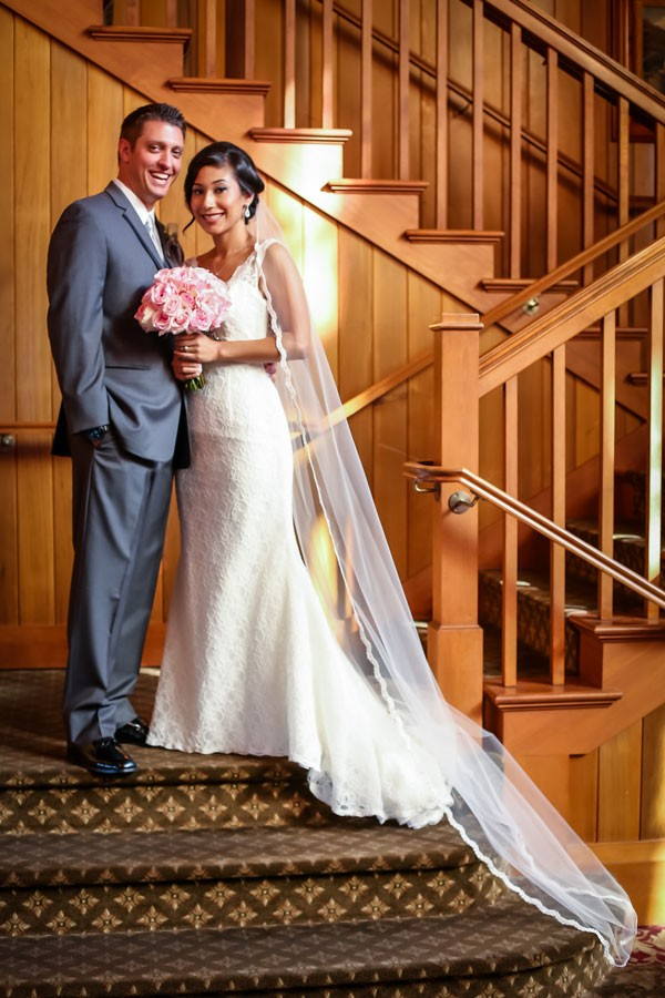 bride and groom stand on large staircase at venue