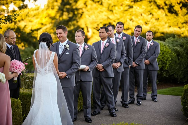 line of groomsmen in gray suits at altar