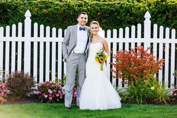 bride in strapless sweetheart wedding dress and groom in gray suit stand in front of picket fence