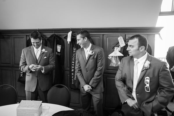 groom opening gift while groomsmen get ready for ceremony