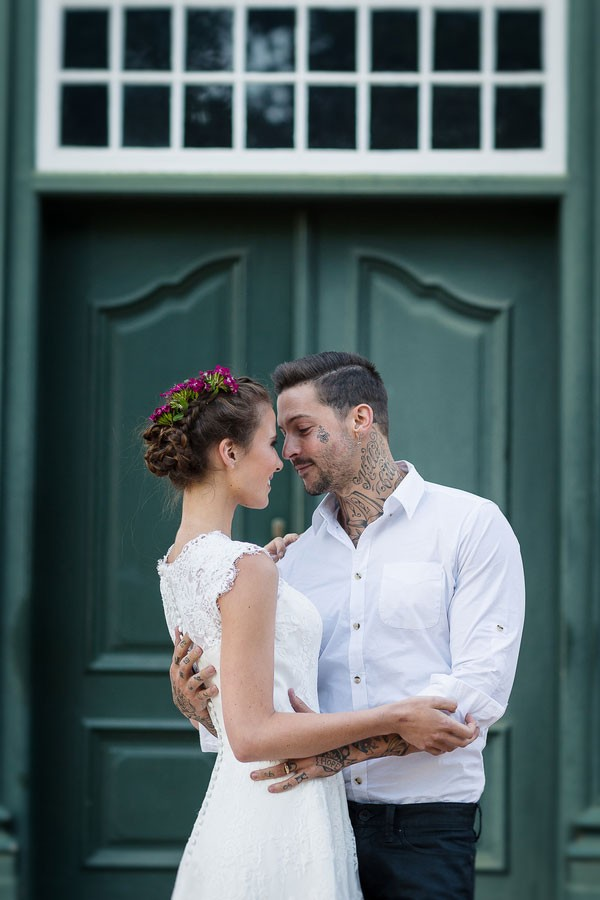 groom holds bride with flower decorated, braided updo