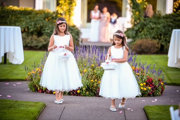 flower girls in white dresses and pink sashes