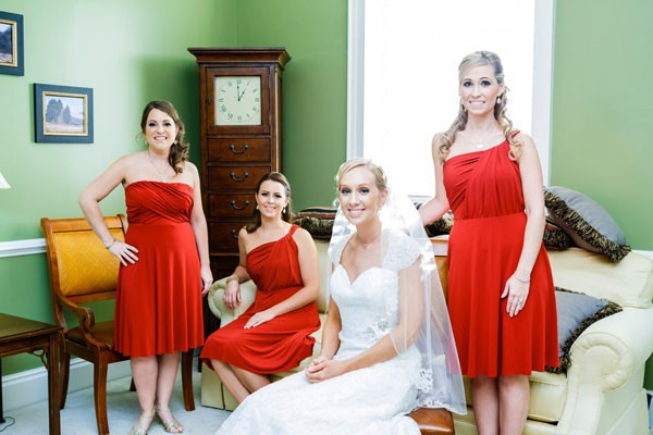 bridesmaid in knee length scarlet dresses with bride