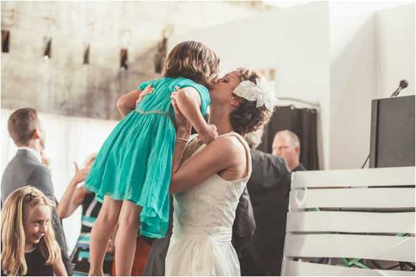 bride holds up little girl in green dress for a kiss
