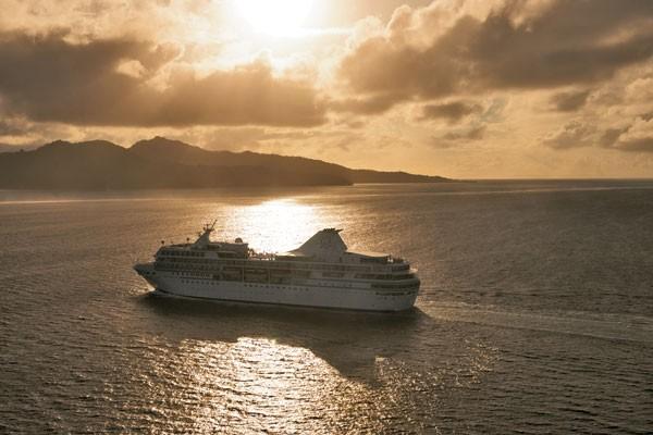 Paul Gauguin cruise ship sailing across sea at sunset