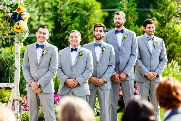 groom and groomsmen in light gray suits and mismatched blue bow ties