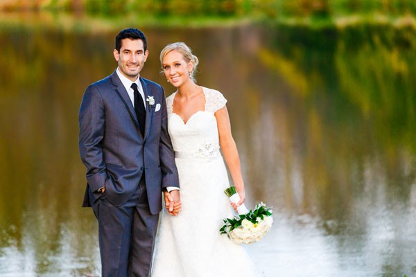 bride and groom stand by lake during autumn