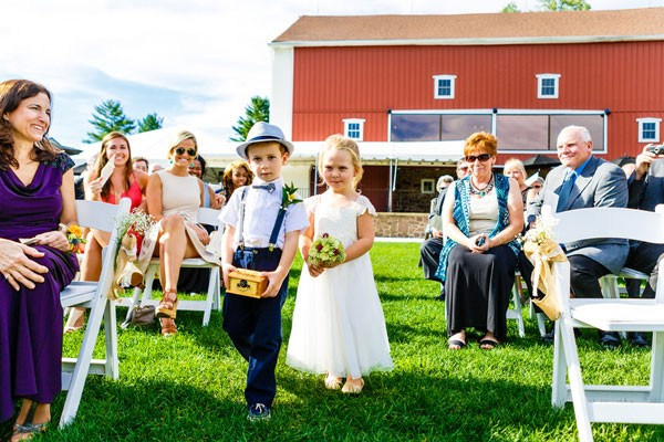 ring bearer in suspenders and bow tie and flower girl in white dress with small bouquet
