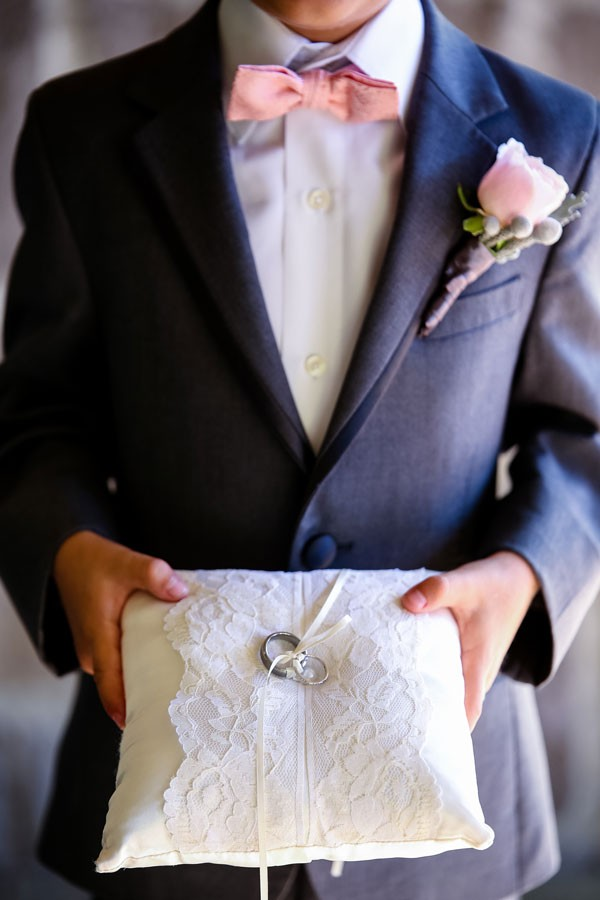 ring bearer with pink bow tie and ring pillow