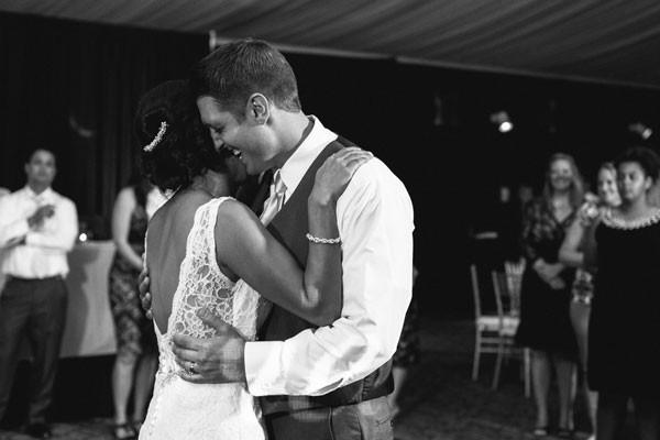 grooms laughs as bride whispers something in his ear