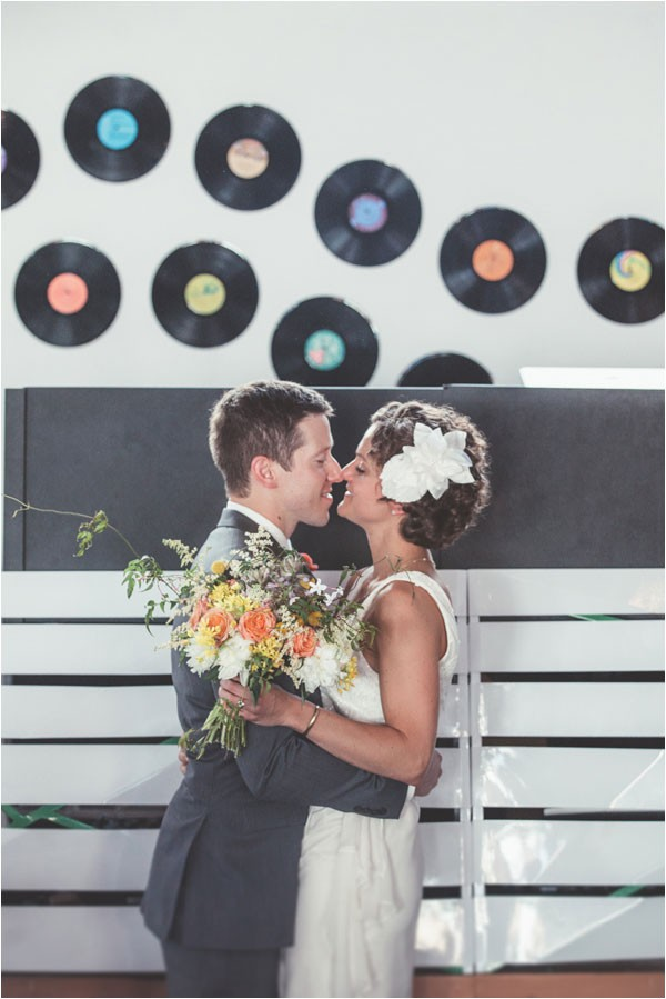 modern bride and groom kiss in front of vinyl record backdrop
