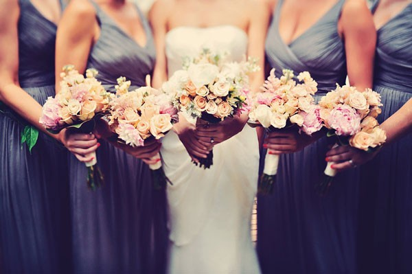 bridal party in charcoal gray dresses surround bride