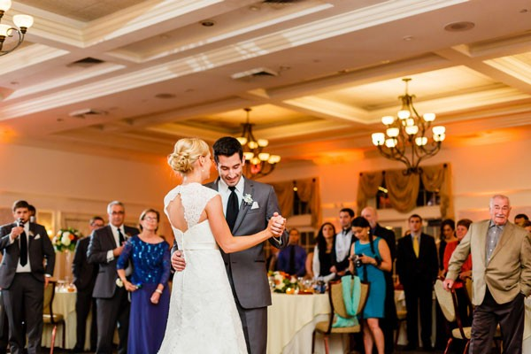 first dance at reception with bride in statement back wedding dress and groom in gray suit
