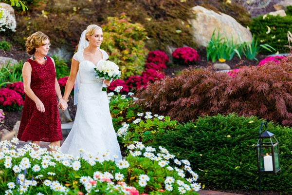 mother of bride walks her daughter through garden towards ceremony