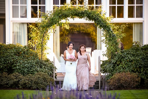 mother walks daughter down the aisle under a garden arch