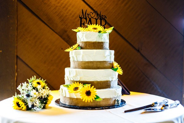 buttercream wedding cake decorated with burlap and sunflowers