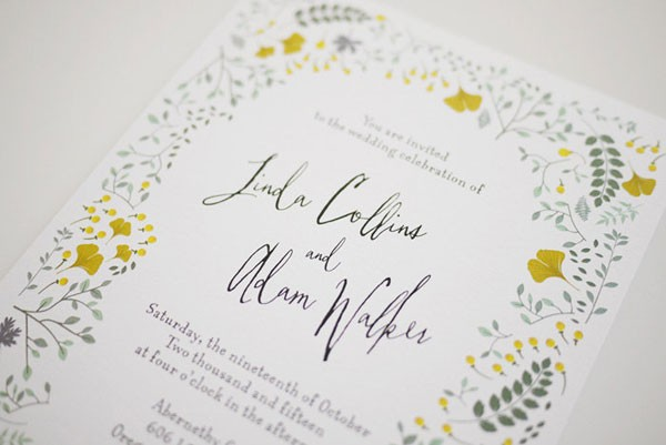 wedding invitation with pale floral border and cursive script