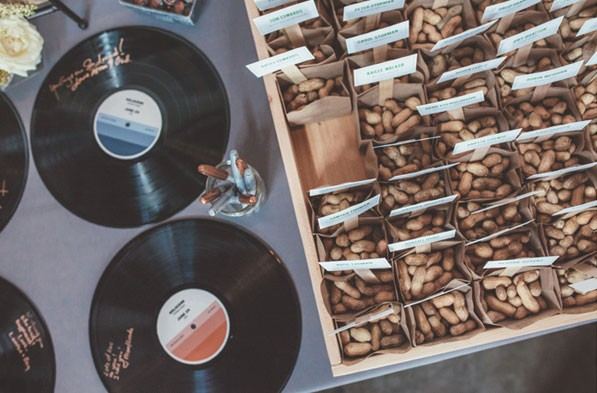 vinyl record guest book and bags of peanuts for guests at welcome table