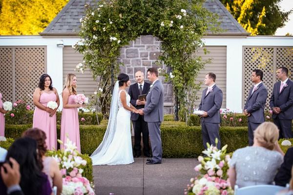 garden wedding ceremony under lush, leafy arch