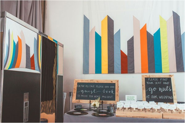 welcome table in front of mural at modern wedding