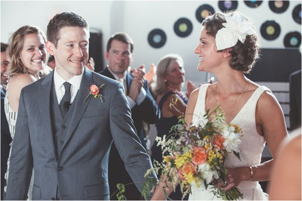 bride and groom in gray suit walk back down aisle after ceremony
